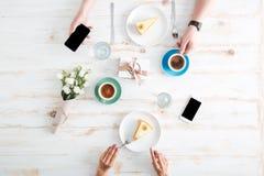Mani delle coppie che mangiano i dolci e che per mezzo degli smartphones sulla tavola Fotografia Stock