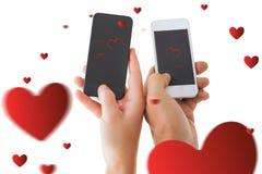 Mani delle coppie facendo uso del telefono cellulare contro fondo bianco Fotografia Stock Libera da Diritti