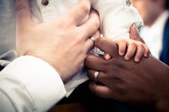 Mani delle coppie interrazziali con il bambino Immagine Stock