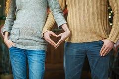 Mani delle coppie nella forma del cuore di amore Rosa rossa Immagine Stock