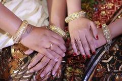 Mani delle coppie nuziali nelle nozze di Giava immagini stock libere da diritti