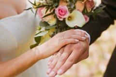 Mani delle coppie sulla cerimonia nuziale Immagine Stock