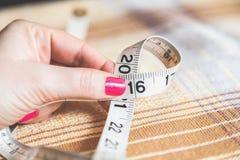 2016 mani delle donne che tengono centimetro di cucito Fotografie Stock Libere da Diritti