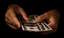 Mani delle donne con i pacchetti dei dollari Fotografia Stock