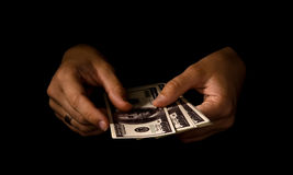 Mani delle donne con i pacchetti dei dollari Fotografie Stock