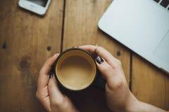 Mani delle donne con il computer portatile ed il caffè sulla vista del piano d'appoggio fotografia stock libera da diritti