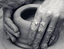 Mani delle donne in corso della fabbricazione della ciotola dell'argilla sulla ruota delle terraglie fotografie stock
