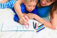 Mani delle lettere di scrittura del bambino e della madre Immagine Stock