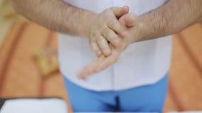 Mani dello sfregamento del terapista di massaggio del primo piano facendo uso di olio video d archivio