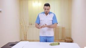 Mani dello sfregamento del terapista di massaggio facendo uso del primo piano dell'olio archivi video