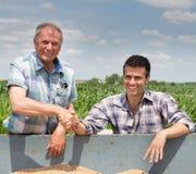 Mani dello shakig degli agricoltori sul mucchio dei grani Fotografia Stock Libera da Diritti