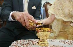 Mani dello sposo e della sposa che versano acqua cerimoniale Immagine Stock