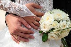 Mani dello sposo e della sposa con gli anelli di cerimonia nuziale Immagine Stock