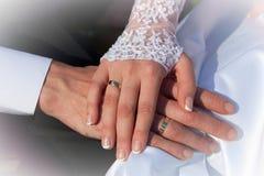 Mani dello sposo e della sposa con gli anelli di cerimonia nuziale Fotografie Stock