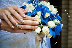 Mani dello sposo e della sposa con gli anelli di cerimonia nuziale Fuoco molle Immagini Stock