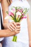 Mani dello sposo e della sposa con il mazzo dei callas Immagini Stock