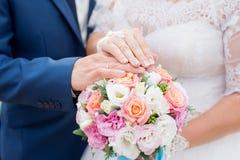 Mani dello sposo e della sposa con il mazzo dei fiori e delle fedi nuziali Concetto di amore e del matrimonio immagini stock