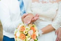 Mani dello sposo e della sposa con le fedi nuziali e le rose dei fiori Concetto di amore e del matrimonio immagini stock