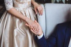 Mani dello sposo e della sposa con le fedi nuziali sui fiori Fotografia Stock