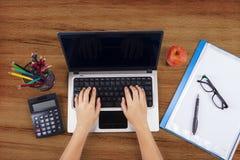 Mani dello studente che scrivono sul computer portatile Immagine Stock