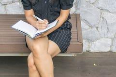 Mani destre femminili con scrittura della penna sul taccuino su erba fuori Fotografie Stock