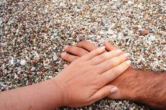 Mani di Alacati nelle pietre della foto sulle mani della spiaggia, della femmina e del maschio Fotografie Stock