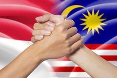 Mani di associazione con le bandiere indonesiane e malesi Immagini Stock