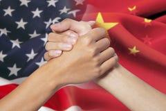 Mani di associazione con Russo e le bandiere americane Immagini Stock