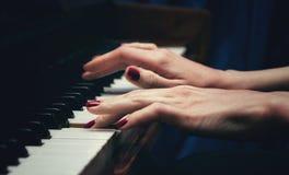 Mani di bella giovane donna che gioca il piano Vista laterale Fuoco selettivo spaceBlur della copia immagine stock libera da diritti
