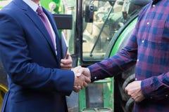 Mani di And Businessman Shaking dell'agricoltore con il trattore nel fondo Immagini Stock Libere da Diritti