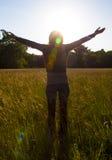 Mani di diffusione della ragazza con gioia ed ispirazione che affrontano il sole, saluto del sole Immagini Stock