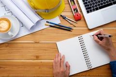 Mani di Engineerman con il taccuino di scrittura della penna Fotografie Stock Libere da Diritti