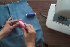 Mani di giovane rotazione del sarto la bobina del filo contro lo sfondo di una gonna tagliata di tessuto blu La macchina per cuci fotografia stock libera da diritti
