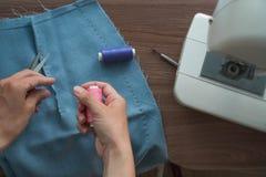 Mani di giovane rotazione del sarto la bobina del filo contro lo sfondo di una gonna tagliata di tessuto blu La macchina per cuci fotografie stock