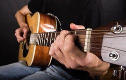 Mani di giovane tipo che gioca la chitarra Immagine Stock