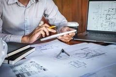 Mani di ingegneria o dell'architetto di costruzione che lavorano all'ispezione del modello in posto di lavoro, mentre controlland fotografia stock libera da diritti