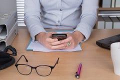 Mani di invio di messaggi di testo della donna di affari in ufficio luminoso immagine stock libera da diritti