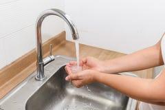 Mani di lavaggio con il flusso continuo dell'acqua in cucina fotografie stock libere da diritti