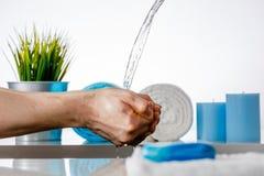 Mani di lavaggio sotto acqua corrente nel bagno Fotografia Stock