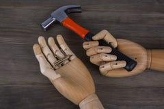 Mani di legno che tengono i martelli ed i chiodi Fotografia Stock