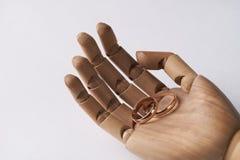 Mani di legno prostetiche con due fedi nuziali Fotografia Stock