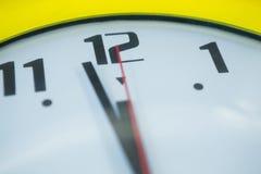 Mani di orologio che raggiungono una mezzanotte di 12 orologi Immagini Stock