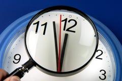 Mani di orologio del primo piano circa per colpire mezzanotte o mezzogiorno tramite la lente d'ingrandimento Fotografia Stock Libera da Diritti