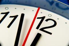 Mani di orologio del primo piano circa per colpire mezzanotte o mezzogiorno tramite la lente d'ingrandimento Immagini Stock