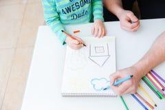 Mani di piccolo disegno del padre e del figlio con gli indicatori variopinti fotografia stock libera da diritti