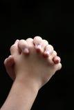 Mani di preghiera sincere di un bambino Immagini Stock