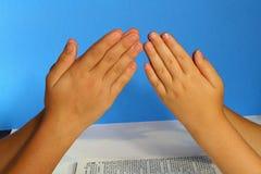 Mani di preghiera sull'azzurro Immagini Stock Libere da Diritti
