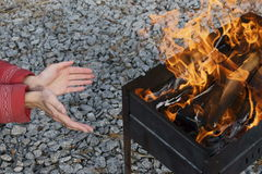 Mani di riscaldamento dal fuoco fotografia stock