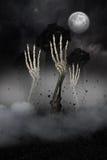 Mani di scheletro che scoppiano dalla tomba Fotografia Stock