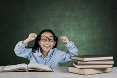 Mani di sollevamento sorridenti della ragazza con i libri in aula Immagine Stock Libera da Diritti